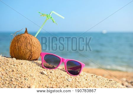Tropical coconut with drinking straw and sunglasses at the summer beach