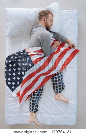 American citizen. Nice patriotic pleasant man holding a US flag and sleeping while being an American patriot