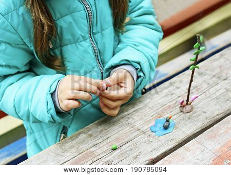 Child to play outdoors. The image is part of small child playing with plasticine in the street behind the mahogany Desk. A child plays with clay and various natural materials with different shapes.