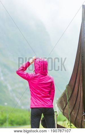 Female tourist standing near old wooden viking boat in norwegian nature looking at misty mountains. Rainy foggy day. Tourism and traveling concept