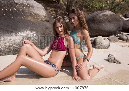 Two beautiful Bikini models girls posing sexy at tropical stone beach location. Vogue style