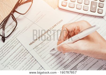 Hand writes the personal information on the health insurance claim form