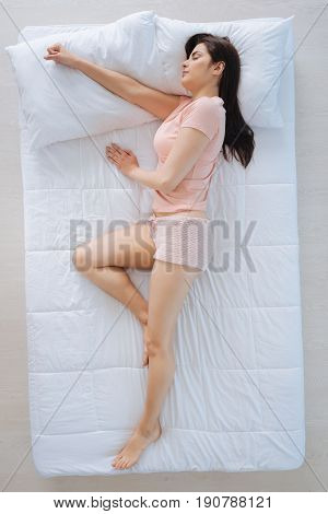Everyone needs rest. Attractive nice pleasant woman sleeping and having dreams while lying comfortably on her bed