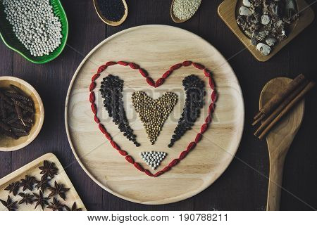 Spices and herbs in wooden Plate with heart concept. Food and cuisine ingredients