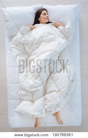 I feel warm. Delighted nice pleasant woman lying under the blanket and sleeping while feeling warm