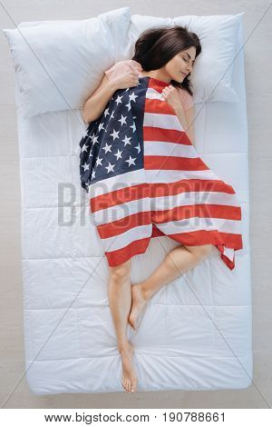 My country. Delighted pleasant nice woman lying on her back and being covered with American flag while sleeping