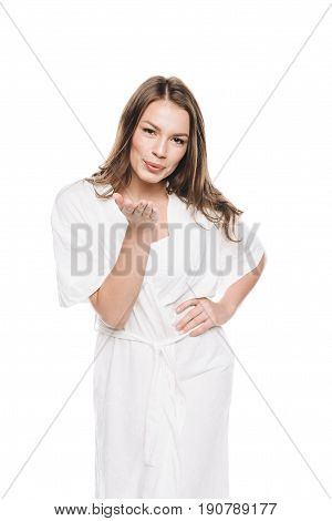 Portrait Of Young Woman In White Robe Blowing A Kiss At Camera Isolated On White