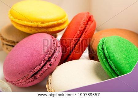 Colorful macaroons isolated on white background. French macaroons in a paper box