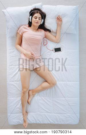 Pleasant entertainment. Joyful positive delighted woman lying on the bed and wearing headphones while listening to music