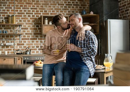 Happy Homosexual Couple Holding Glasses Of Orange Juice And Kissing At Home