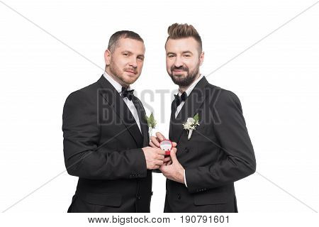 Smiling Homosexual Wedding Couple In Suits Holding Wedding Rings And Looking At Camera