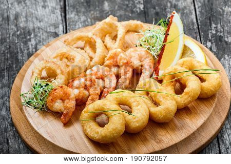 Seafood platter with deep fried squid rings shrimp and onion rings decorated with lemon on cutting board on wooden background. Mediterranean appetizers. Top view