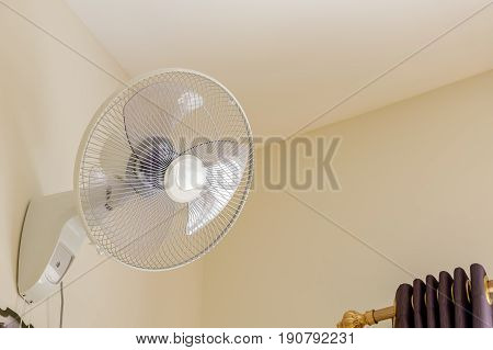 Close up fan on the wall in the bedroom.