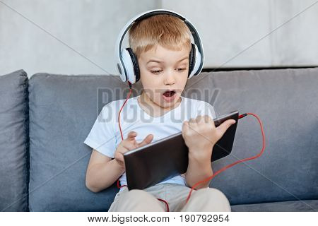 Oh my Gosh. Nice creative clever kid using a tablet and searching something in the web while sitting on a couch and wearing headphones