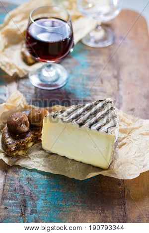 Sweet dessert liqueur wine in glass hard french cheese Tomme de Montagne and dried figs with figs bread still life