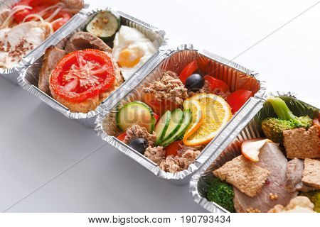 Healthy food background. Healthy lunch in foil containers. Daily take away restaurant meals. Steamed meat with fresh and cooked vegetables in boxes on white background