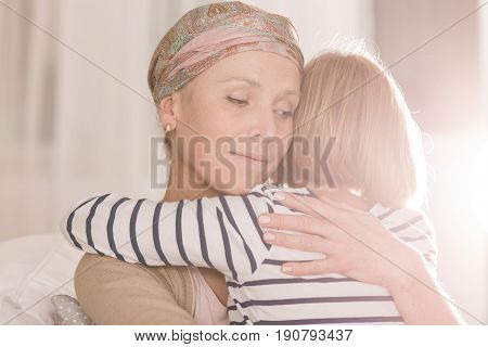 Worried woman with cancer cradles her child