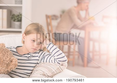 Sad daughter with teddy bear worries about her ill mother