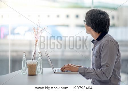 Young Asian business man dressed in casual style working in coffee shop with his laptop computer. Digital nomad and IT modern lifestyle Co working space for freelance jobs