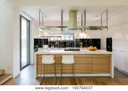 Open plan of kitchen area with a modern kitchen island chairs and kitchen amenities