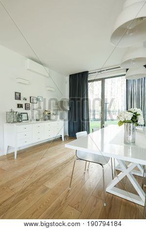Well-lighted dining room with minimalistic table chairs lamp commode and patrio entry