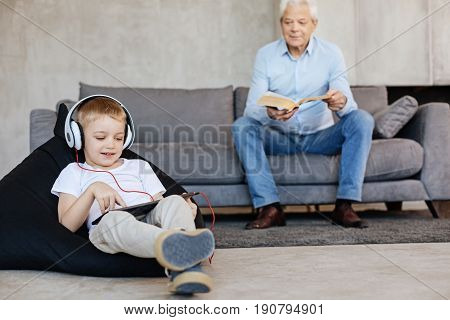 Different ages. Clever savvy young kid and his grandpa using different means for reading while spending time at home and doing what they liking