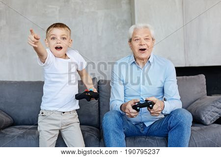 Run that way. Two cool cheerful generations of men being real boys and enjoying the game while spending free time together at home