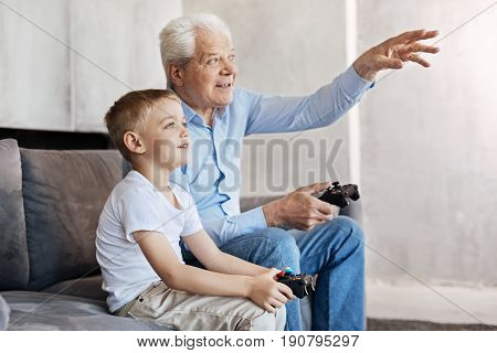 Common interest. Adventurous sociable nice gentleman and his kid becoming real buddies with his grandson as they sharing common passion for video games