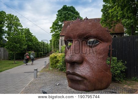 Canterbury Kent England - May 15 2017: The face Mask or Bulkhead art created by Rick Kirby British sculptor sitting outside Marlowe Theatre at the city of Canterbury Kent UK.
