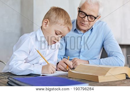 Write carefully. Diligent smart motivated boy working on some math equations while his grandpa assisting him and acting as his tutor