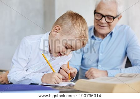 Diligent student. Awesome active wise gentleman sitting at the table assisting his grandson while he making his home assignment