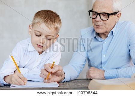Try changing this. Thoughtful neat persistent kid working on his home assignment while his grandpa checking the tasks and explaining his blunders