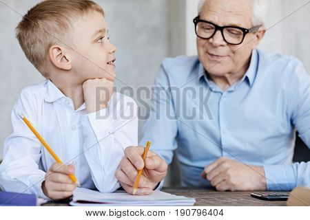 Personal tutor. Clever interested original kid sitting at the table and waiting while grandpa helping him and checking his home assignment
