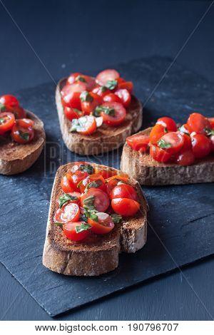 tomato bruchetta slices on a black background
