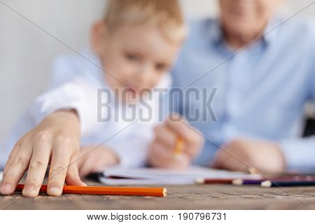 Come here. Nice enthusiastic excited kid taking a tool for making notes while working on his home assignment with his grandpa