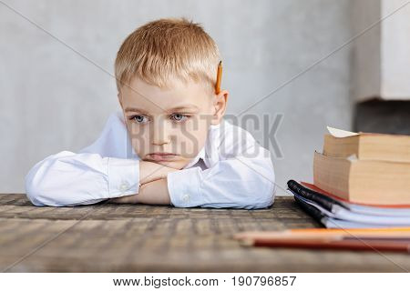 Not my thing. Disappointed tired young kid refusing fulfilling home assignment while sitting at the table