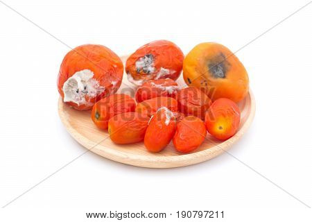 rotten tomato on wooden plate isolated on white background