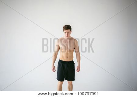 Portrait Young Sexy Handsome Man Of Strong Athlete's Body With Bare Torso, Dressed In A Black Sports