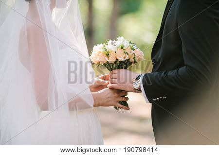 the groom in a black suit gives to the bride in white dress with veil a wedding bouquet outdoor. date, engagement, romantic, love, feeling, event concept. wedding ceremony.