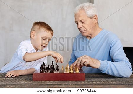 Developing thinking. Nice clever elderly gentleman spending time with his grandson and enjoying an intellectual game while sitting at the table