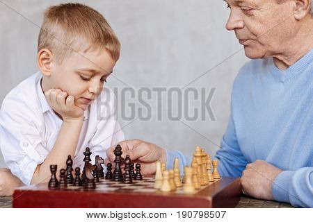 Training problem solving. Clever attentive nice guy teaching his grandson plying chess while he listening him attentively