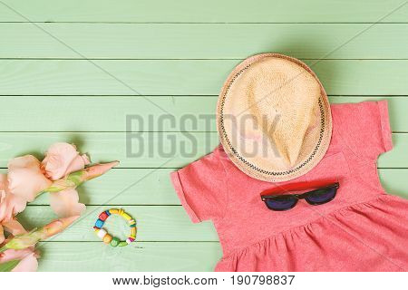 Set Of Baby Girl's Clothes On Wooden Background