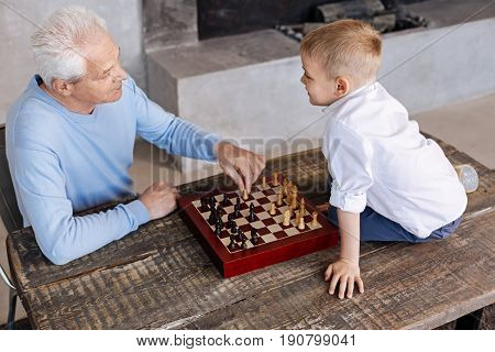 Loving the feeling. Enthusiastic charming mature man giving his grandson a lecture on how playing chess while they spending some time together