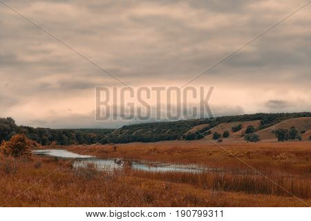 Fisherman in a boat on a small lake in a cloudy hilly valley.