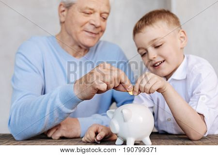 Sharing life wisdom. Clever handsome mature guy teaching his grandson about some basic economic principles while illustrating his speech with vivid examples