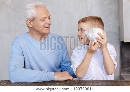 Explaining money. Diligent serious bright man educating his grandson about economy and giving him a piggy bank for saving money