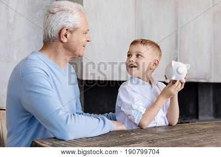 How money work. Cute curious nice kid seeming fascinated with what his grandparent saying while listening to him attentively