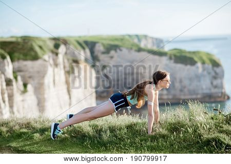 Young woman in sportswear training outdoors on the beautiful rocky background