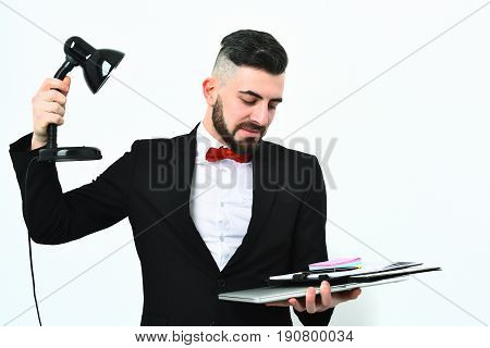 Bearded Boss Holds Lamp And Lights On Laptop With Stationery