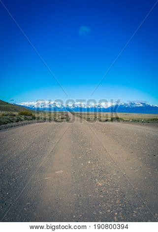Gravel road in patagonia leading to the mountains